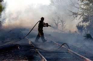 ###Ocala Star-Banner, Grass fire , Silver Springs Shores FL - Contact photographer at 352-598-7976### A Marion County Fire Rescue fire fighter and EMT Cory Parrot(cq) is busy spraying water in the area of the CSX Rail Road, near Bahia Court Way and Bahia Court Track, Thursday afternoon, March 2, 2006, Silver Springs Shores, FL. ( Jannet Walsh/Star-Banner)2006