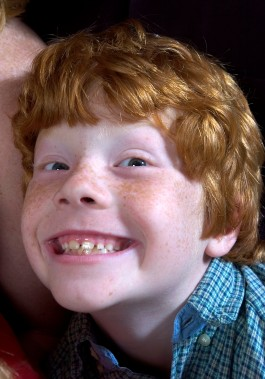 ###Rare Redhead: Michael and LuAnne Warren family of five redheads and red haired dog, Ocala### Redheaded parents LuAnne Warren, 42, and Michael Warren, 36, do their best to sit with their three active red haired boys. Here is Matthew Warren, 8, with his wide smile having fun with Jenny the Golden Retriever, also a redhead, Monday evening, April 11, 2005, Ocala, FL, USA. (Jannet Walsh/Star-Banner)2005