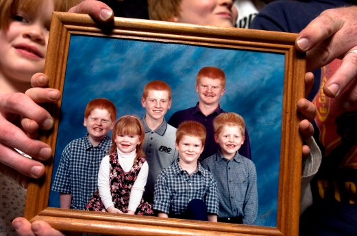 ###Rare Redhead: Family of eight redheads: Russell and Linda Rock, both redheads, and their six redheaded children, of the Florida Highlands### In the beginning there was just Linda Russell, 47, and her husband Russell Rock, 48, both redheads, that married 22 years ago. Russell's red hair has grayed and become darker, with a receding hairline. Today they have six children, all with red hair, with the ages of 8 to 21. Here the children hold a portrait of themselves from 2001. The family of redheads all live together, Monday evening, April 25, 2005, Florida Highlands, FL, USA. (Jannet Walsh/Star-Banner)2005