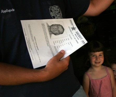###Belleview Police visit Sex offenders### Chris Applegate holds a flyer he received from Belleview Police Detective Larry Thompson of a neighbor, sex offender Mark R. Nelson. Right is Applegate's daughter Isis Applegate, Wednesday morning, May 11, 2005, Belleview, FL, USA. (Jannet Walsh/Star-Banner)2005