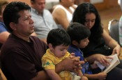"""Freelance for The Florida Catholic - Catholic Center Our Lady of Guadalupe, Ocala - CONTACT PHOTOGRAPHER/writer Jannet Walsh 352-598-7976 - cell### Left to right, Nicanor Trujillo holds his son Nick Trujillo age 2, while son Juan Trujillo (cq) age 9, sings along with wife Patricia Trujillo , all of the """"Little Mexico """" area in Ocala. The family is originally from Guerrero, Mexico and has lived in the United States since 1987, three years in Ocala. They attend Mass at Catholic Center Our Lady of Guadalupe. The Catholic center serves as a church, education center and health clinic located in an area called """"Little Mexico"""" in rural Ocala. The center is located close to several area horse farms that employ many Hispanics, many from Mexico, Tuesday evening, June 21, 2005, in Ocala, FL. (Jannet Walsh/Freelance for The Florida Catholic)2005"""
