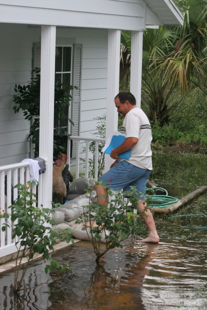 ###NEWS - Silver Springs Shores home located at 6 Peacon Run Harbor is flooded, Silver Springs Shores- CONTACT PHOTOGRAPHER 352-598-7976 - cell### Drew Pearce (cg) with closing papers from house, walks in the water the front steps of his house located at 6 Peacon Run Harbor. Pearce and his wife purchased the home on June 23, 2005, and now are flooded with water covering their property, Thursday evening, July 14, 2005, in Silver Springs Shores, FL. ( Jannet Walsh/Star-Banner)2005