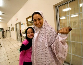 Ocala Star-Banner - Ramadan 2005, evening breaking of fast party Saturday, Oct. 22, 2005, Ocala, FL. Islam project: Azza Mousa of Ocala, right, originally from Egypt, holds her small version of the Koran, written in Arabic, standing outside of the entrance to women's section of the prayer room at the time of Ramadan. She is giving a hug to Natasha Bonthron age 8 at the time of Ramadan, after they finished with prayers. The breaking of fasting party, during the holy month of Ramadan in 2005, that involves the fasting of food during the day. The Ocala Islamic Center, located on Northeast 14th Street, celebrated the evening of Saturday, Oct. 22, 2005 with a party hosted by Dr. Humeraa Qamar and her husband Dr. Asad Qamar of Ocala, that included food, prayer, fellowship. In the prayer rooms, men and women are separated by a white curtain, the faithful gather for one of the times of daily prayer, Saturday evening, October 22, 2005, Ocala, FL. ( Jannet Walsh/Star-Banner)2006