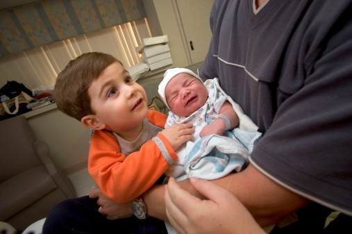 """###Ocala Star-Banner - First baby of 2006 in Marion County, born at MRMC, Ocala FL - contact photographer at 352-598-7976### Danielle Stevens(cq) right, her and is center, with husband Shaun Stevens (cq) holds the new baby boy Asher Stevens(cq), with brother Noah Stevens (cq) age 2 years, left, all in a hospital room at MRMC. Asher (cq) was the first baby born in Ocala for 2006, arriving at 2:45 am, weighing 8 pounds and 11 ounces and 20 inches in length. The new baby's brother Noah Stevens (cq) age 2 years, the mother's husband Shaun Stevens (cq) including the Mary Leidecker (cq), the baby's great-grandmother, all of Hernando, were on hand to visit the new arrival. The baby was delivered by Linda Reilly (cq) a certified nurse midwife, according to the Danielle Stevens(cq). The mother's labor lasted about 9 hours and went """"beautifully"""" compared to her first that baby's birth, Noah, that lasted 36 hours. """"We hope he has an opportunity to be blessed as we are. We both want him to be healthy, learn and the grow, """" stated Danielle Stevens, Sunday afternoon, January 1, 2006, Ocala, FL. ( Jannet Walsh/Star-Banner)2005"""