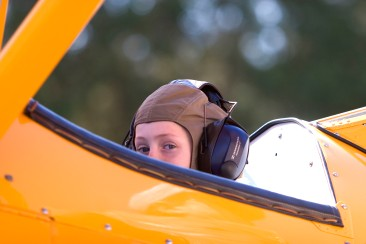 ###Ocala Star-Banner - Camp Fly for kids to learn about flying, Belleview, FL### Andrea Froom(cq) age 7, of Ocala, wearing a pilot's helmet was a passenger of pilot Tim Kirby(cq) flying his Stearman 1941 biplane to demonstrate to students at Camp Wings at at Back Achers Airfield to learn about flying, Saturday morning, Nov. 4, 2006, Belleview, FL. ( Jannet Walsh/Star-Banner)2006